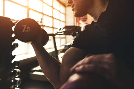 Young male athlete performs exercises with dumbbells in the gym. Strength training.