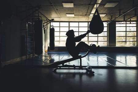 Crossfit strength training of a man with a punching bag and doing press exercises in the gym. Silhouette shot in front of the window. 写真素材