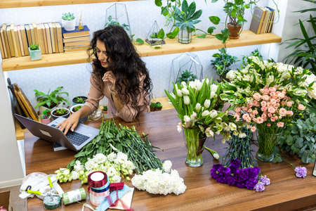 Attractive young woman florist is working in a flower shop. Working on a laptop