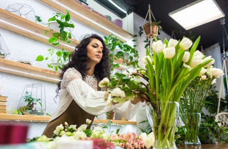 Attractive young woman florist is working in a flower shop. 写真素材