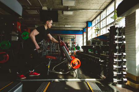 Young male athlete performs exercises with dumbbells in the gym. Strength training