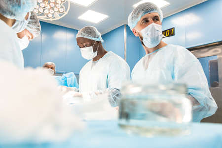 An international team of doctors performs a complex surgical operation on a patient under anesthesia. Modern operating room and experienced surgeons save lives 写真素材
