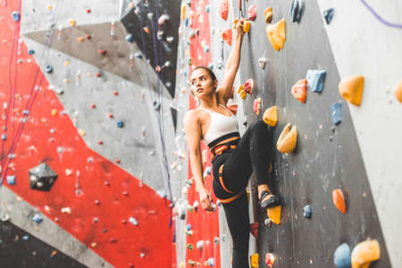 Sportswoman climber moving up on steep rock, climbing on artificial wall indoors. Extreme sports and bouldering concept
