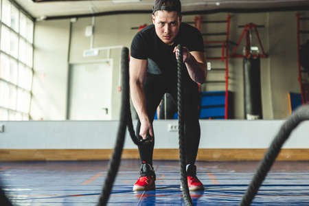 Portrait shot of strong young man training with battle ropes in the exercise gym