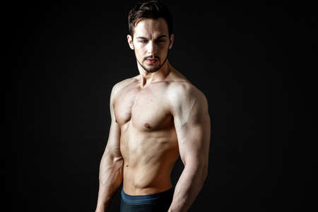 Portrait of a handsome muscular sportsman on a dark background