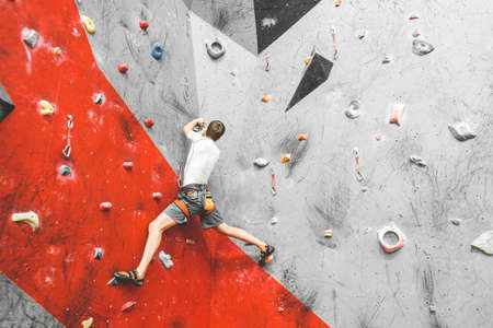 Sportsman climber moving up on steep rock, climbing on artificial wall indoors. Extreme sports and bouldering concept 写真素材