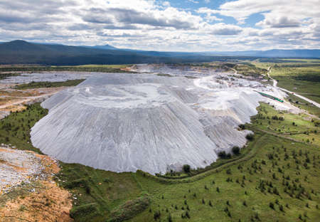 aerial top view of soda and limestone quarry and large white embankments against the backdrop of green summer nature