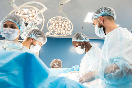 An international team of doctors performs a complex surgical operation on a patient under anesthesia. Modern operating room and experienced surgeons save lives