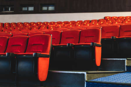 Cinema interior. Red armchairs in a large empty cinema hall. Pandemic and crisis in the industry Фото со стока