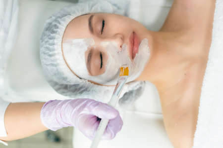 Facial skin care and protection. A young woman at a beauticians appointment. The specialist applies a cream mask to the face