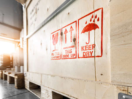 Bright red special marking symbols on wooden boxes with goods inside, prescribing careful handling of the cargo