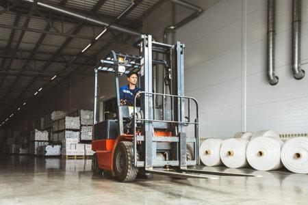Forklift loader for warehouse works outdoors with risen forks