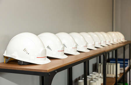 White protective engineering helmets lie in a row on a shelf in a factory, Industrial safety and labor protection Фото со стока