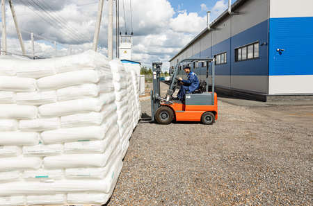A man on a forklift works in a large warehouse, unloads bags of raw materials into a truck for transportation