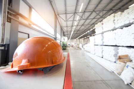 Protective orange hard hat close up on the background of industrial factory interiors