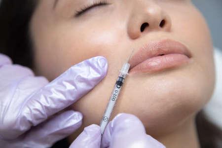 Woman doing rejuvenation procedure, close-up syringe near face