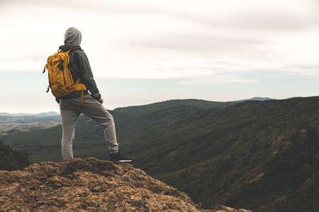 A man in hiking clothes with a yellow backpack stands on the top of a hill among the mountains around and in the background Фото со стока