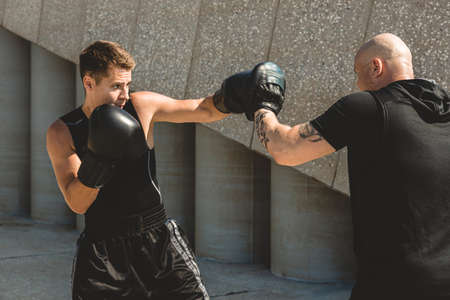 Two men exercising and fighting in outside. Boxer in gloves is training with a coach Фото со стока