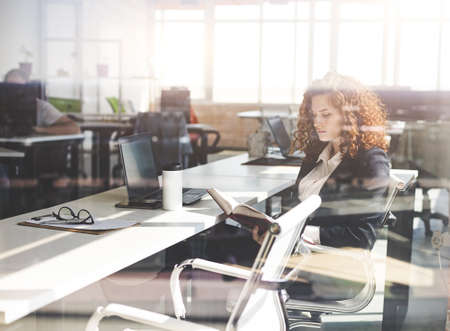Portrait of a beautiful young business woman with red curly hair working productively in the office. Successful career and staff of a large company