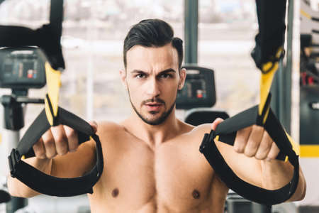 Handsome young sporty male bodybuilder with naked torso doing exercises in the gym Фото со стока
