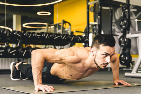 Handsome young sporty male bodybuilder with naked torso doing push-up exercise in the gym