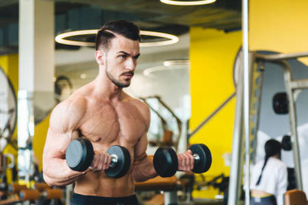 athletic man doing dumbbell exercise in front of a mirror bare torso in the gym