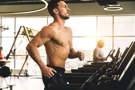 Handsome young sporty male bodybuilder with naked torso doing exercise on the treadmill in the gym Фото со стока