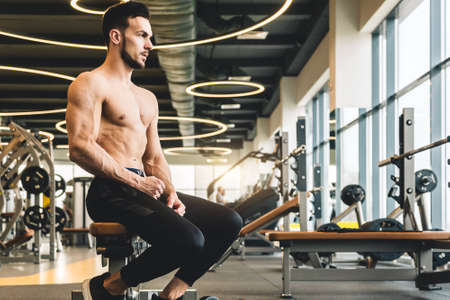 Handsome young sporty male bodybuilder with naked torso sits resting between exercises Фото со стока
