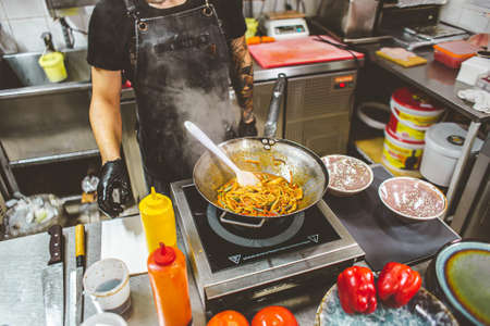 street food. fried noodles in a wok with chicken and shrimp on the wok. Фото со стока