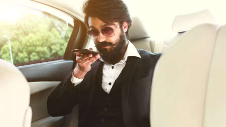 Stylish handsome Hindu businessman with glasses and a beard works in the backseat of the car and uses the phone. Safe and comfortable luxury travel