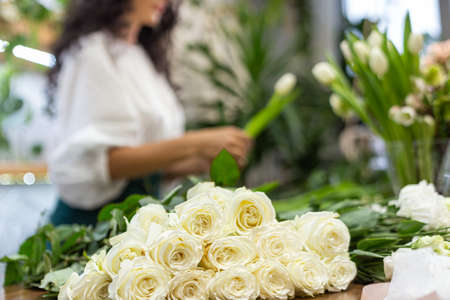 Attractive young woman florist is working in a flower shop. Фото со стока