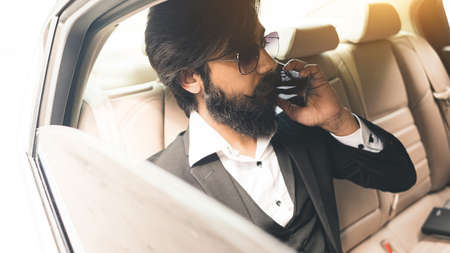 Stylish handsome Seo Hindu with glasses and a beard talking on the phone in the back seat of the car. Safe and comfortable business travel Фото со стока