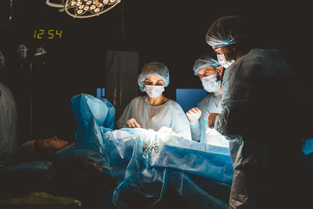 The senior surgeon in the operating room, where the patient is waiting for him, and he begins the operation. Real Modern Hospital with Authentic Equipment. Фото со стока