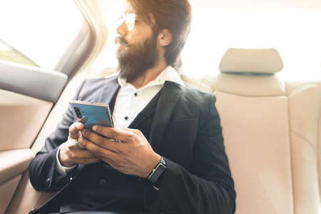 Stylish handsome Hindu boss with glasses and a beard works with the phone in the back seat of the car. Safe and comfortable business travel