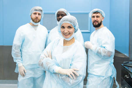 Portrait of a team of doctors in uniform and medical masks after completion of a surgical operation Фото со стока