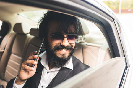 Stylish handsome Seo Hindu with glasses and a beard is talking on the phone in the back seat of the car. Safe and comfortable business travel