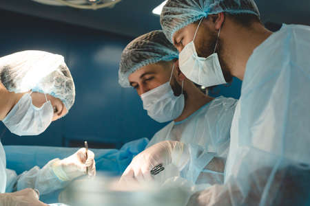 An international team of doctors performs a complex surgical operation on a patient under anesthesia. Modern operating room and experienced surgeons save lives Фото со стока