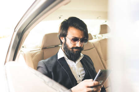 Stylish handsome Hindu businessman works in the backseat of the car and uses the phone. Safe and comfortable luxury travel