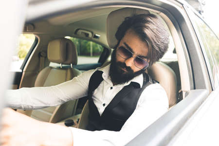 Stylish and successful Indian in a stylish suit driving a luxury car. The best cars and conditions for your business
