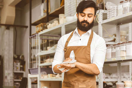 Portrait of a young businessman craftsman with a beard and mustache in his workshop. He wipes his hands with a napkin after work, standing on the background of shelves with finished products Фото со стока
