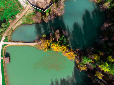Top view of a beautiful blue lake among the autumn forest.