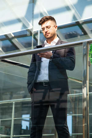 Portrait of a businessman in suit are standing on the background of glass offices.
