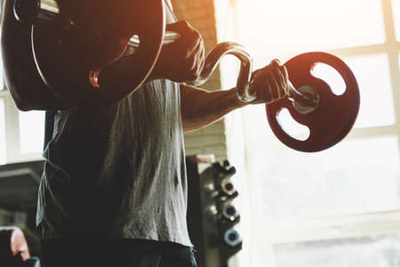 Silhouette photo of a muscular young athlete doing exercises with a barbell in the gym. Power training close up