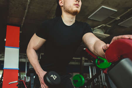 young male athlete performs exercises in the gym with dumbbells. Endurance Strength Training