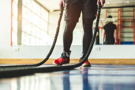 Crossfit with ropes. The athlete is training in the gym.