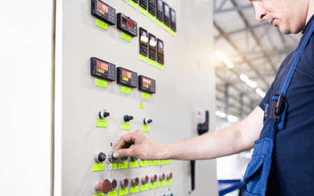 A worker presses a button and starts an automatic manufacturing process in a factory