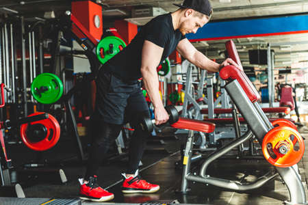 Portrait of a muscular man performs exercises in the gym. Strength training with dumbbells