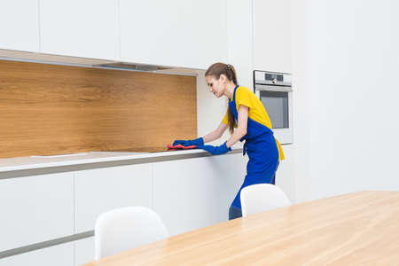professional cleaning service. Two women in working uniform, in aprons, divide the cleaning of the kitchen of a private house, cottage. washing the refrigerator, tap, sink. Wash floor. Фото со стока