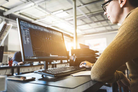 Engineer designer working on desktop computer in factory Фото со стока