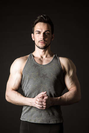 Awesome portrait of a handsome sporty model on a dark background